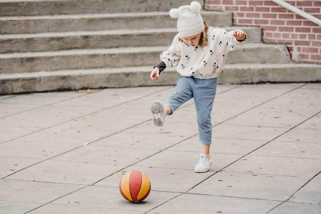 Kind In Blauw En Wit Polkadotjack En Blauwe Denimjeans Basketbal Spelen