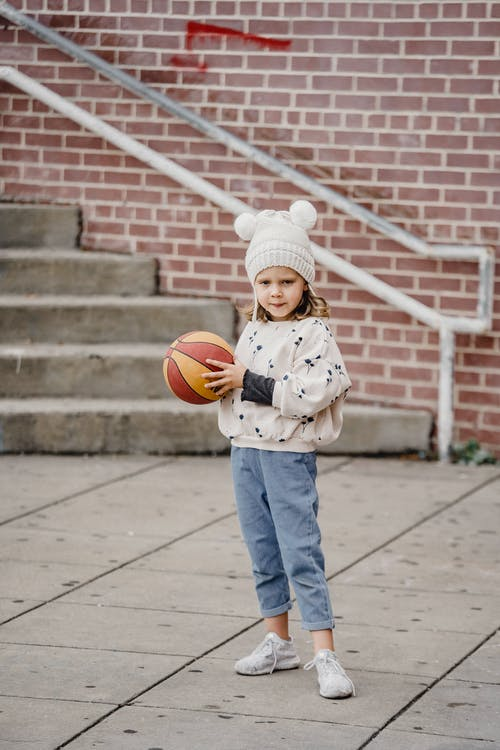 Little girl with colorful ball beside stairs on street