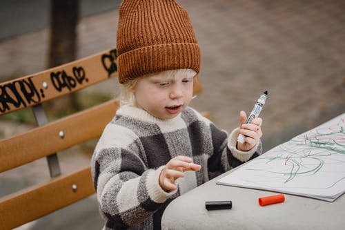 Cute little boy drawing with markers in sketchpad in park