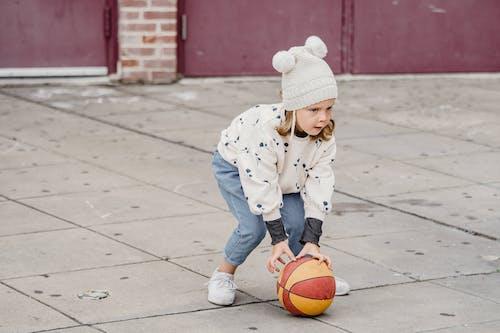 Cute little girl pulling ball on street