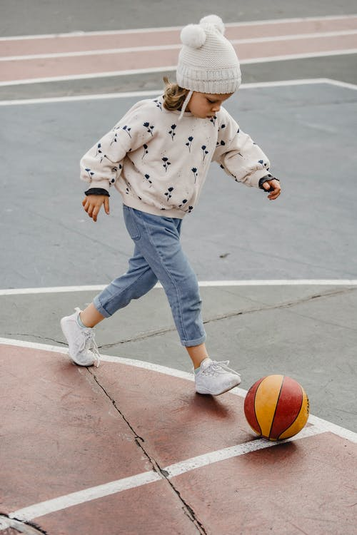 Cute girl walking after ball on sports ground