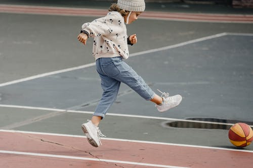 Side view of jumping little girl in jeans and jumper kicking colorful ball playing on sports yard