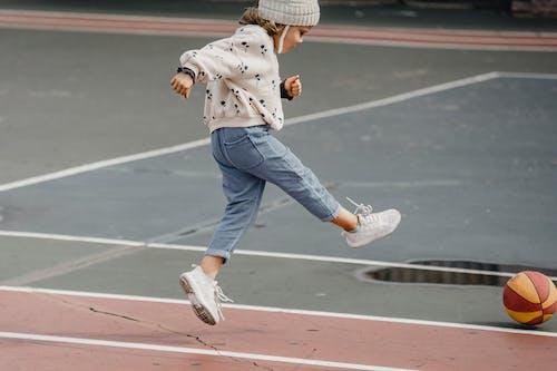 Person In Blue Denim Jeans Und Brown Coat Walking On Track Field