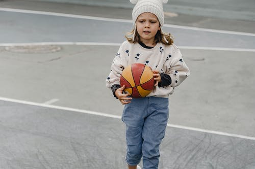 Little girl with colorful ball in sports yard at daytime