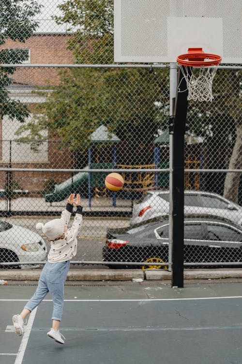 Side view full body of unrecognizable little kid throwing ball into hoop while playing game on sports ground on street
