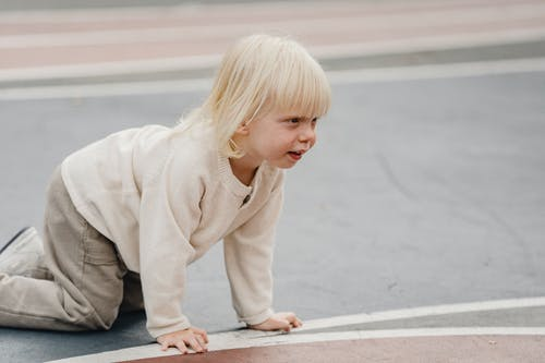 Cute little boy crawling on playground