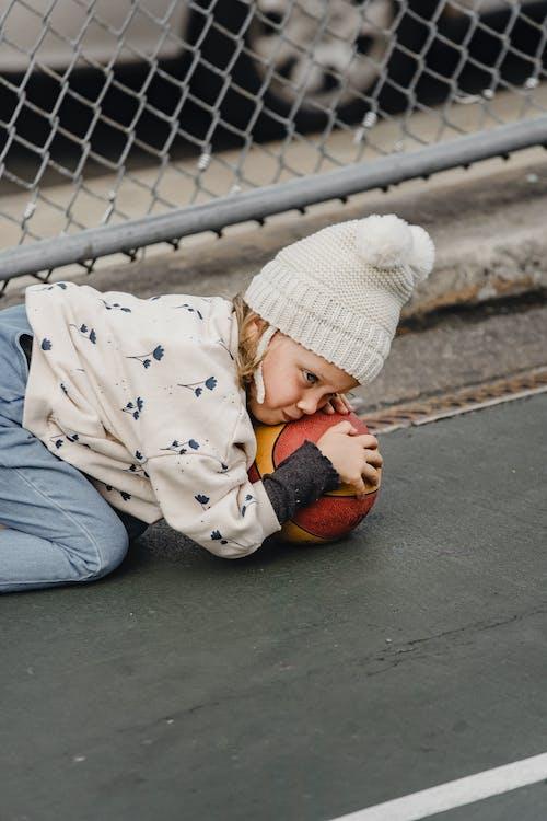 Kind In Witte En Zwarte Jas Liggend Op Betonnen Vloer
