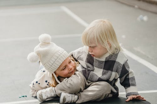 Cute little boy and cute girl in hat cuddling while lying on sunny sports ground on street against blurred background