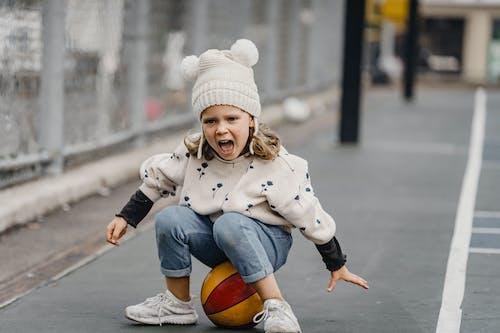 Cute emotional girl sitting on ball