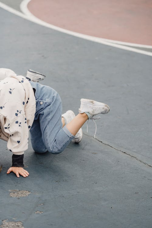 Side view of anonymous playful little kid wearing jeans and sneakers standing on all fours on green shabby sports ground