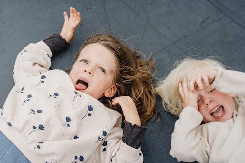 Meisje In Witte En Zwarte Trui Liggend Op Grijze Betonnen Vloer