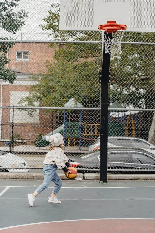 Unrecognizable girl playing basketball on sports ground