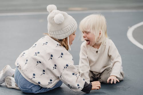 Side view of cute little girl with hat and playful boy showing tongue sitting on sports ground while having fun against blurred background
