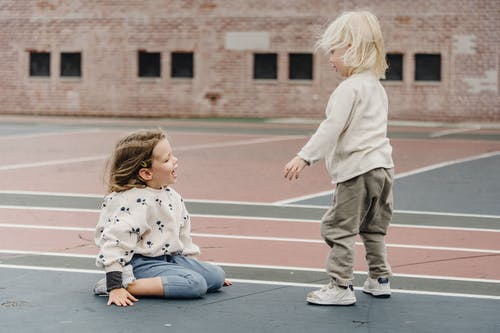 Playful siblings playing on playground