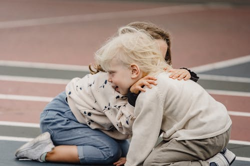Anonymous tender girl embracing cute little boy with blond hair while sitting on colorful sports ground together  on blurred background