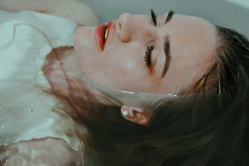 Woman resting in bathtub with eyes closed