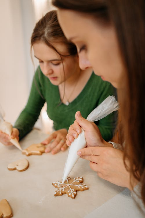 Two Girls Decorating Christmas Cookies With Icing