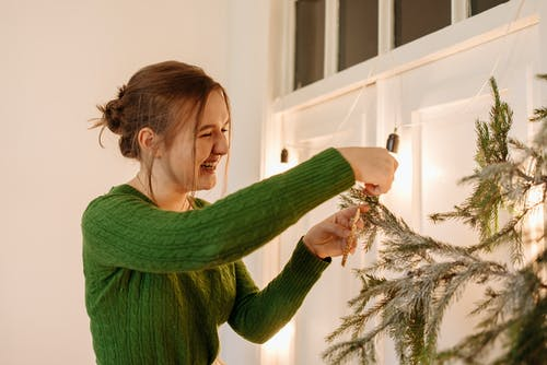 Woman in Green Sweater Hanging A Decor On The Christmas Tree