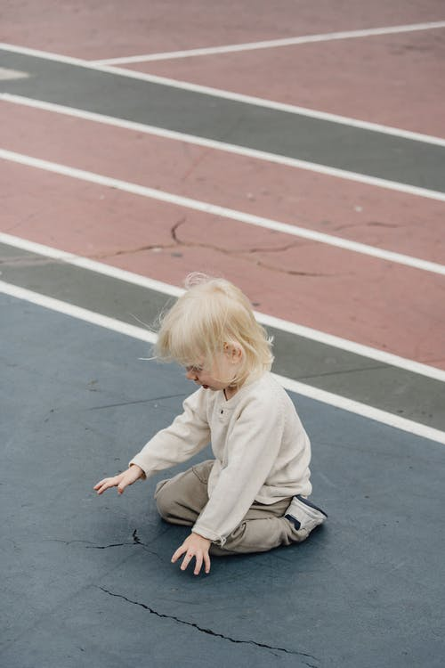 From above full body side view of adorable curious kid with blond hair sitting on track of colorful sports ground