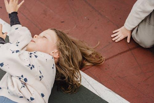 Vrouw In Wit En Blauw Star Print Shirt Liggend Op Rode Betonnen Vloer