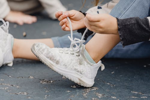 Unrecognizable child with bent leg tying laces on dirty footwear while sitting on playground on street with anonymous kid on blurred background