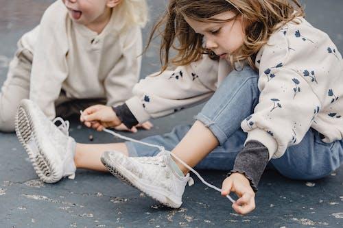 Crop girl tying shoelaces on playground