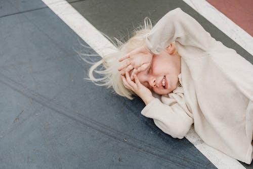 Vrouw In Wit Shirt Met Lange Mouwen Liggend Op Grijze Betonnen Vloer