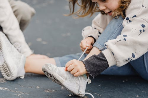 Crop girl tying laces on sneakers