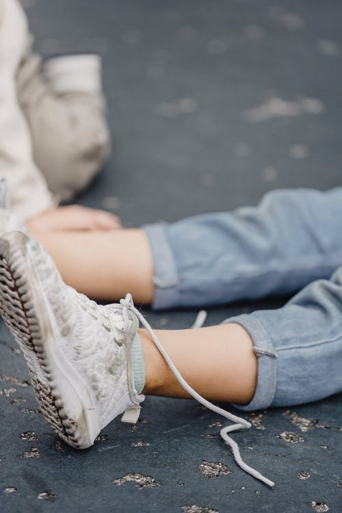Unrecognizable kid in jeans with untied shoelaces on white dirty footwear sitting on playground with anonymous child on blurred background