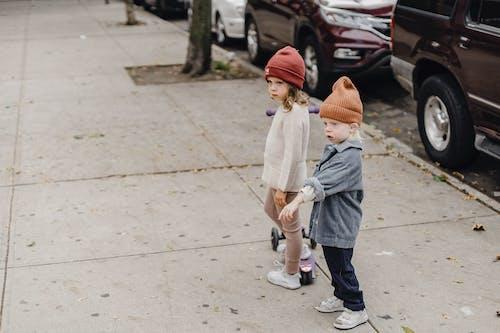 Stylish siblings standing on sidewalk