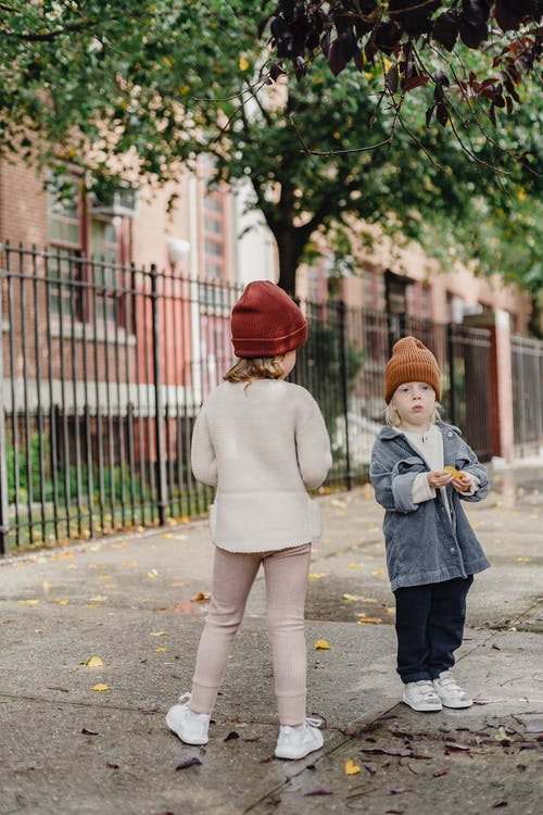 Full body of cute unrecognizable girl and boy wearing hat standing on pathway on street with metal grid and green tree