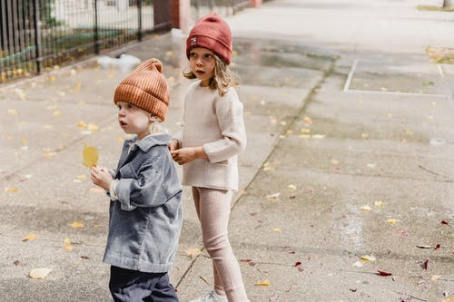 Cute little siblings wearing hats with fallen leaf in hand standing on pathway with dried foliage on street with metal fence