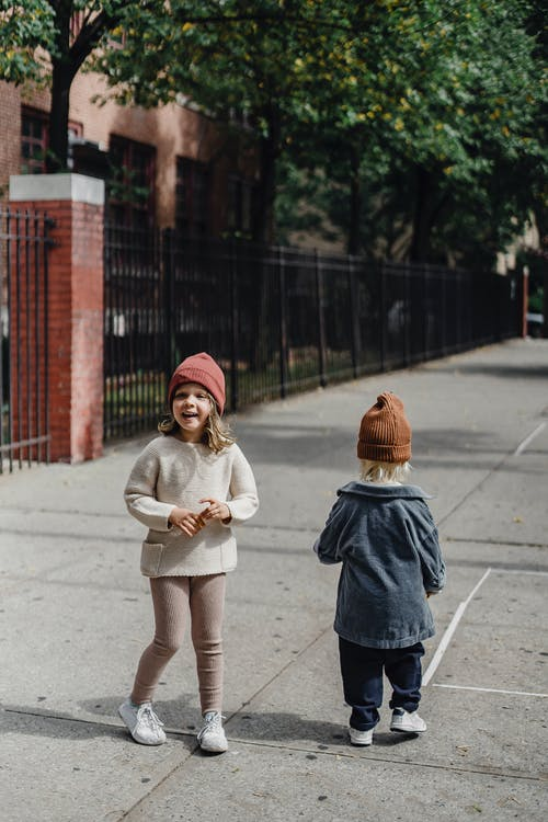 Full body of little anonymous boy and girl in hat strolling on pathway on street with metal fence and building