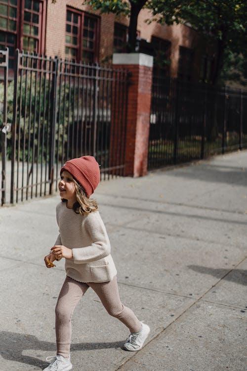 Stylish girl walking on sidewalk