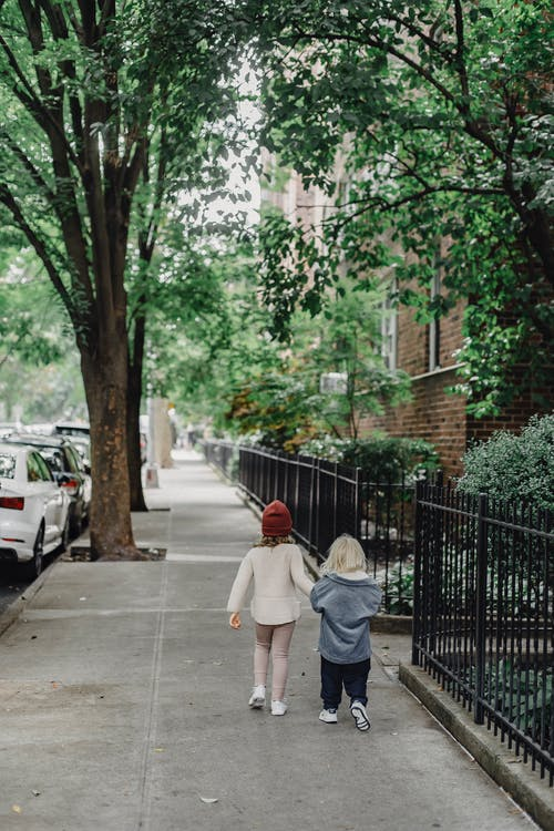 Full body back view of anonymous boy and girl strolling on pathway along metal fence and green trees on street