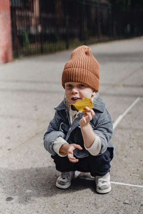 Full body of adorable kid in hat with yellow withered leaf in hand looking at camera while squatting on pathway on street