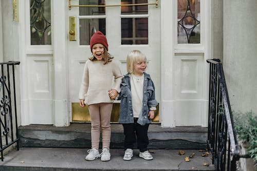Full body of positive girl in hat and boy holding hands while standing on doorstep near entrance of house on street