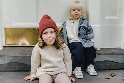 2 Mädchen Mit Strickmütze Auf Betonbank Sitzend