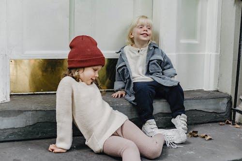 2 Girls Sitting on Gray Concrete Floor