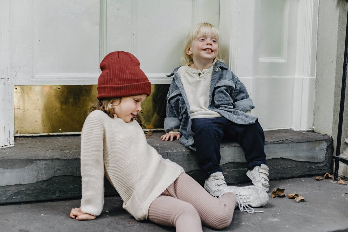 2 Girls Sitting on Gray Concrete Floor
