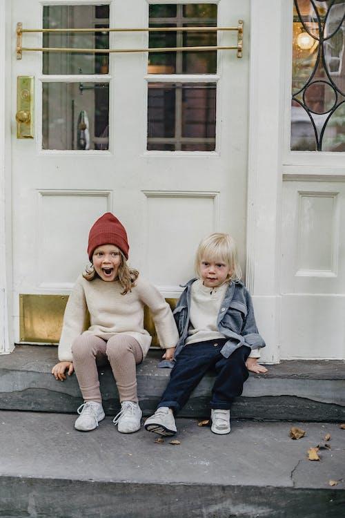 Full body of playful girl in hat sitting near little boy on doorstep near door of residential building on street