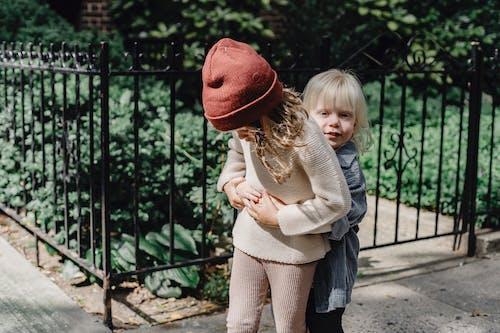 Frau Im Braunen Pullover, Der Kind Im Weißen Pullover Trägt