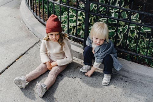 From above full body of adorable little boy and girl in hat sitting on walkway near metal fence on street