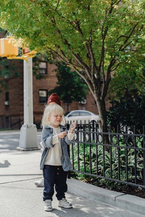 Little boy standing on sidewalk