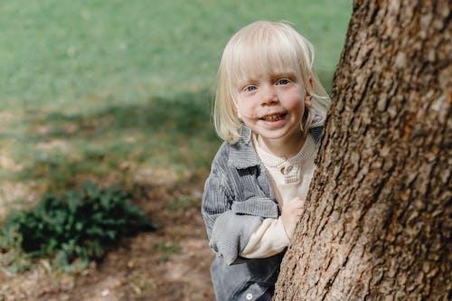 Cheerful little boy standing near tree