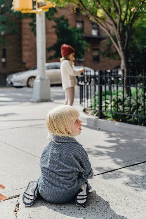 Side view full body of cute boy with blond hair sitting on pathway on street with little girl on blurred background