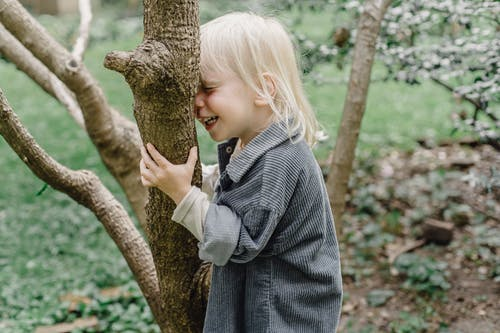 Side view of cheerful little kid with closed eyes smiling and touching tree trunk while standing in park on blurred background