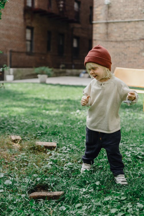 Full body of playful little kid wearing hat standing on grassy ground with toy in hand against residential building on blurred background