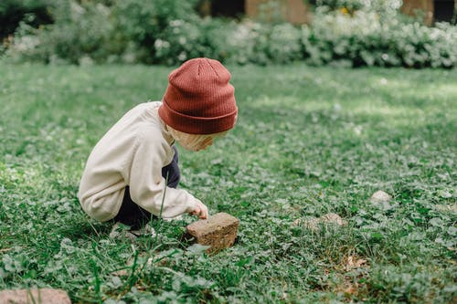 Full body side view of playful kid wearing hat squatting on grassy lawn while exploring small stone against blurred background