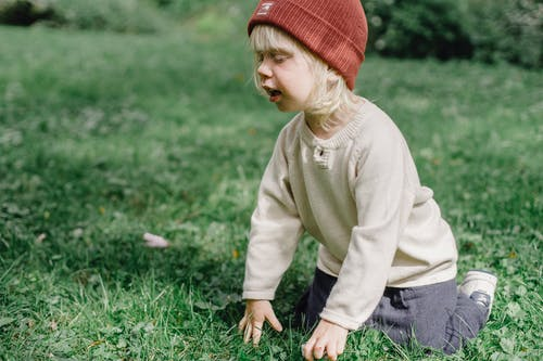 Side view of adorable kid with blond hair in hat sitting on grassy lawn while playing in street on blurred background